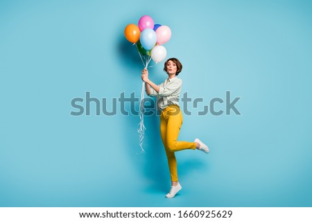 Full size profile photo of funny lady surprise birthday party hold many air balloons playful weekend mood wear casual green shirt yellow pants footwear isolated blue color background #1660925629