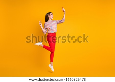 Full size photo funny girl relax fall holidays take selfie smartphone make v-signs video call bloggers influencers wear red pants trousers shoes isolated bright shine yellow color background