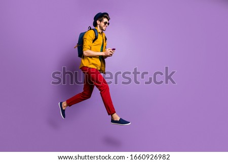 Full size profile side photo of positive guy jump use cellphone search online shopping blogs run after discounts wear blue bag hat yellow shirt red pants isolated violet color background