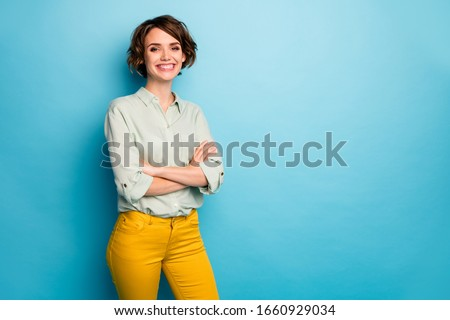 Photo of cool attractive business lady short hairstyle friendly beaming smiling arms crossed good mood wear casual green shirt yellow pants isolated blue color background #1660929034