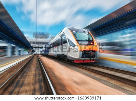 High speed train in motion on the railway station at sunset. Modern intercity passenger train with motion blur effect on the railway platform. Industrial. Railroad in Europe. Commercial transportation #1660939171