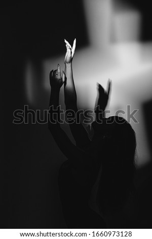 The girl is a dancer, a blonde in a black body, dances in the light of a searchlight, makes waved arms and legs, jumps. black and white photo #1660973128