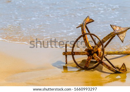 Anchored - Picture of an anchor by the sea shore used to stop the passenger boat from sailing into the Ocean.