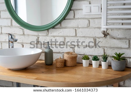Interior of bathroom with modern design. White bricks,design basin and wooden counter with cactus. Bright indoor in industrial style and modern architecture. #1661034373