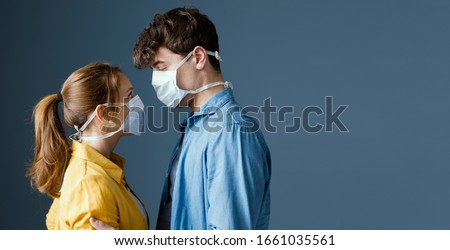 Young romantic loving couple wearing a protective face mask and staring at each other's eyes, pandemic and feelings concept #1661035561