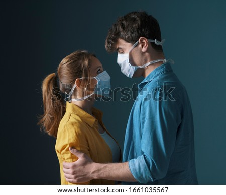 Young loving couple wearing face masks, hugging and staring at each other's eyes, virus spread prevention and feelings concept #1661035567