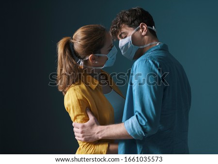 Young millennials couple wearing protective face masks and kissing each other, virus spread prevention and people concept #1661035573