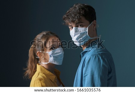 Young couple wearing a protective face mask and looking at camera, flu prevention and health protection concept #1661035576