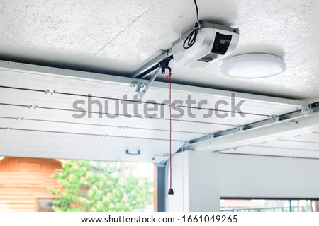 Opening door and automatic garage door opener electric engine gear mounted on ceiling with emergency cord. Double place empty garage interior with rolling entrance gate Royalty-Free Stock Photo #1661049265