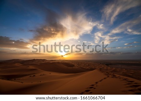Sunset in the Erg Chebbi desert, Morocco. Is part of the Sahara. The sunset is near, the sun on the horizon. There are footsteps on a dune. The sky is cloudy.Sunset in the Erg Chebbi desert, Morocco.  Royalty-Free Stock Photo #1661066704
