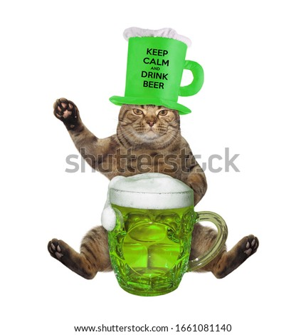 The beige cat in a hat  in the shape of a beer mug is drinking green beer. White background. Isolated.