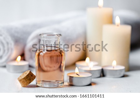 Concept of spa treatment in salon. Natural organic oil, towel, candles as decor. Atmosphere of relax, serenity and pleasure. Anti-stress and detox procedure. Luxury lifestyle. White wooden background  Royalty-Free Stock Photo #1661101411