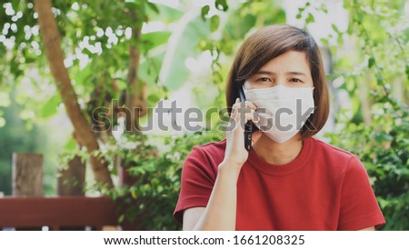 Asian women are sick Due to the virus that spread quickly, she put on a mask to prevent spreading the virus while calling. #1661208325