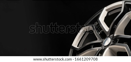 aluminum alloy wheel. Premium cast, the design of the spokes and the wheel rim, a white and black elements on dark background close-up. long layout, copyspace Royalty-Free Stock Photo #1661209708
