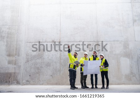 A group of engineers standing against concrete wall on construction site. #1661219365