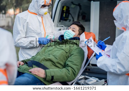 People with protective suits helping man outdoors, coronavirus concept. #1661219371