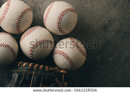 Baseballs flat lay with glove show american softball equipment with copy space, dark moody sports image. Royalty-Free Stock Photo #1661258506
