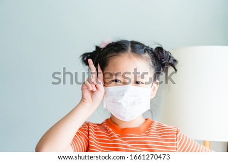 Coronavirus Covid-19 and Air pollution concept.Little chinese girl wearing mask for protect virus and show two finger for fighting quarantine at home.Covid-19 virus outbreak epidemic virus symptoms. #1661270473