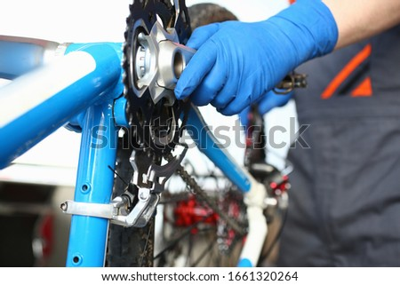 Male bicycle master inspects bicycle mechanism. After-sales service for bicycles. Preparation for new bike season. Avoid unplanned and unexpected damage. Replacing connecting rod system #1661320264