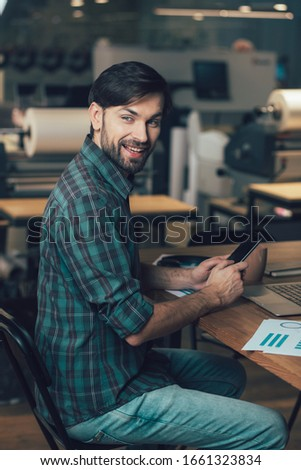 Smiling man in casual clothes sitting at the table with a smartphone and turning back #1661323834