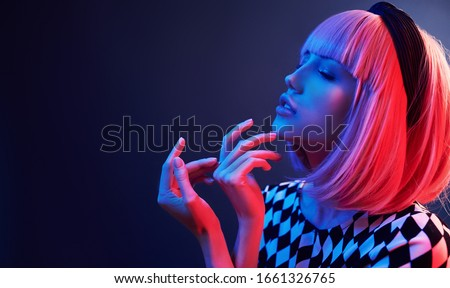 Portrait of young girl with blond hair in red and blue neon in studio. #1661326765