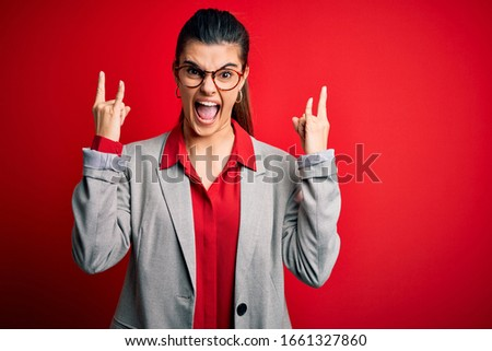 Young beautiful brunette businesswoman wearing jacket and glasses over red background shouting with crazy expression doing rock symbol with hands up. Music star. Heavy music concept. #1661327860