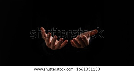 Handsome man sit prayer on black background. His hands are praying for God's blessings. #1661331130