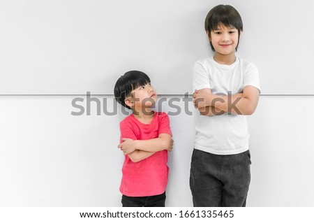 Little child boy standing arms crossed and looking face of tall child at standing arms crossed and smiling. Big and small kid concept at be friends. Royalty-Free Stock Photo #1661335465