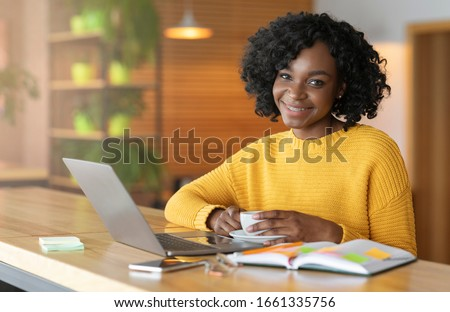 Smiling black woman having coffee break while looking for job online, using laptop at cafe, empty space #1661335756