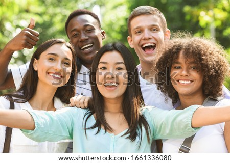 Selfie Fun. Group of multi-ethnic teen friends taking self portrait picture outdoors and sincerely smiling at camera Royalty-Free Stock Photo #1661336080
