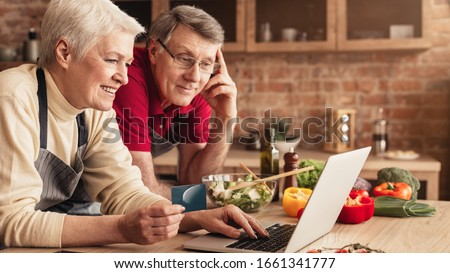 Ordering Food Online. Smiling elderly couple with laptop and credit card purchasing grocery delivery from internet while cooking together in kitchen #1661341777