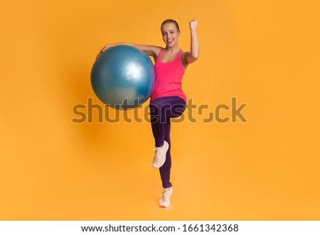 Sporty Lifestyle. Excited Young Woman Jumping With Fitness Ball And Celebrating Success With Raised Fist, Yellow Background, Full-Length Photo #1661342368