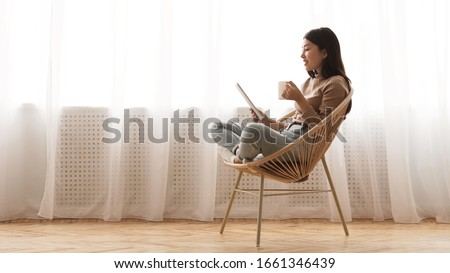 Free time. Girl using tablet and drinking coffee, sitting in wicker chair against window, panorama with free space Royalty-Free Stock Photo #1661346439