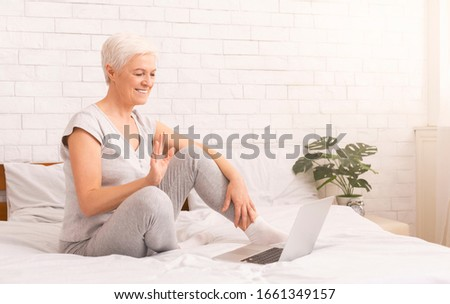 Communication with far living family. Cheerful senior lady talking with friends on laptop online, panorama, empty space #1661349157