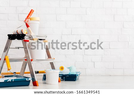 Repair, instruments and materials for painting walls, white bricks wall background, copy space Royalty-Free Stock Photo #1661349541