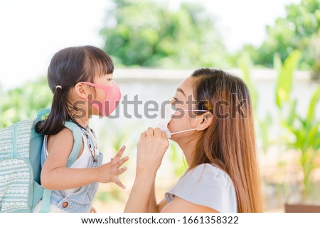 Covid-19 and Air pollution pm2.5 concept.Little chinese girl and chinese mother holding her kid wearing mask for protect pm2.5 in the garden at home.Covid-19 coronavirus and epidemic virus symptoms. #1661358322