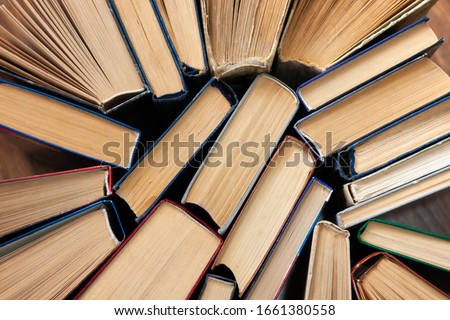 Old and well used hardback books or text books in a book shop or library. Many Books Piles. Hardback books on wooden table top view. Back to school background with copy space #1661380558