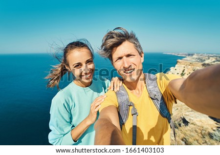 young man and woman tourist making selfie and smile to the camera on cliff edge with beautiful sea view and enjoying wonderful nature. Couple having a great time on vacation. #1661403103