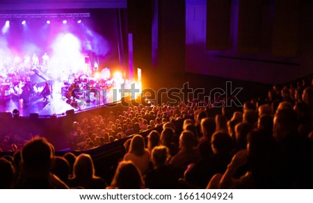 Lights on stage during concert in hall filled with spectators Royalty-Free Stock Photo #1661404924