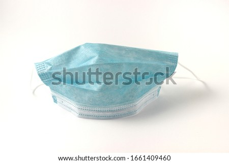 Surgical mask with rubber ear straps. Typical three-layer surgical mask for covering the mouth and nose. Bacteria mask procedure. Protection concept. on white background