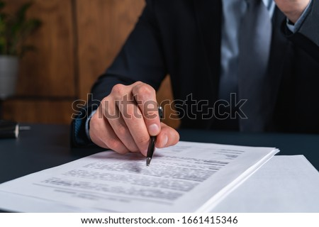 A man signing contract at the office. The concept of entering into partnership.