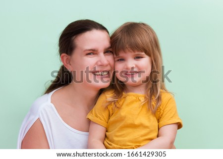 Mother and little kid daughter on pastel mint wall background. Mother's Day love family, parenthood childhoo #1661429305