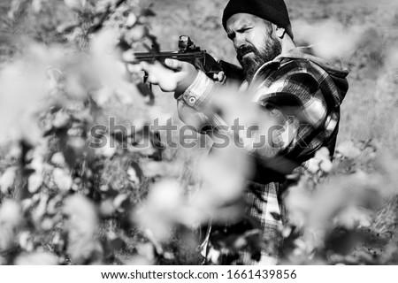 Hunter with a shotgun in a traditional shooting clothing. Hunter with shotgun gun on hunt. Man holding shotgun #1661439856
