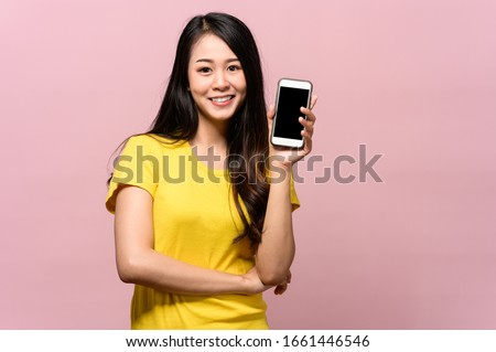 Portrait photo of young beautiful Asian woman holding smart phone with black empty screen on pink background can use for advertising or product presenting concept. Asian woman holding smart phone . #1661446546