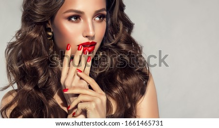 Beautiful model with long curly hair . Fashion trend image , the girl with red manicure on nails. Cosmetics ,makeup and wavy hairstyle  Royalty-Free Stock Photo #1661465731