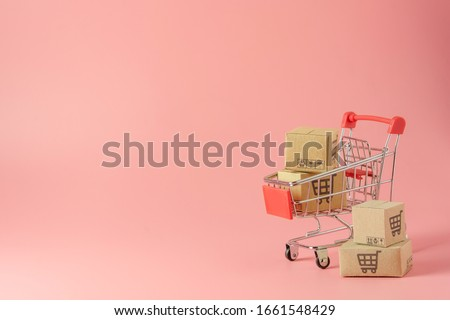 Shopping concept : Cartons or Paper boxes in red shopping cart on pink background. online shopping consumers can shop from home and delivery service. with copy space Royalty-Free Stock Photo #1661548429