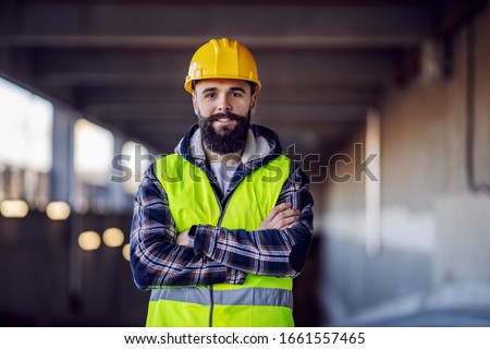 Cute Caucasian bearded construction worker with safety helmet on head in vest standing with arms crossed at construction site and looking at camera. Royalty-Free Stock Photo #1661557465