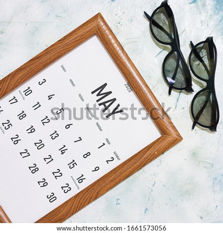May 2020 monthly calendar placed in the wooden picture frame. View from above
