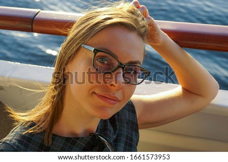 Attractive white business woman in reading glasses smiling on a cruise ship deck in summer at golden hour sunset at sea #1661573953