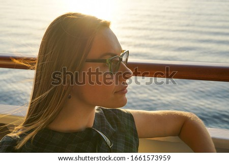 Thoughtful white business woman in reading glasses looking forward sitting on deck of cruise ship in summer at golden hour sunset at sea #1661573959